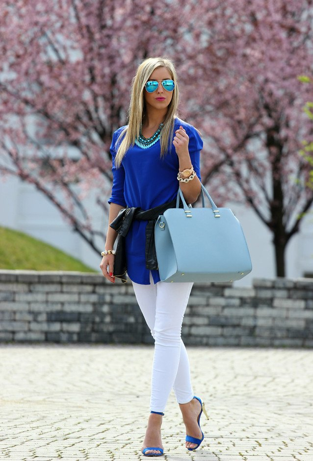 white jeans, a bold blue top and bold blue shoes