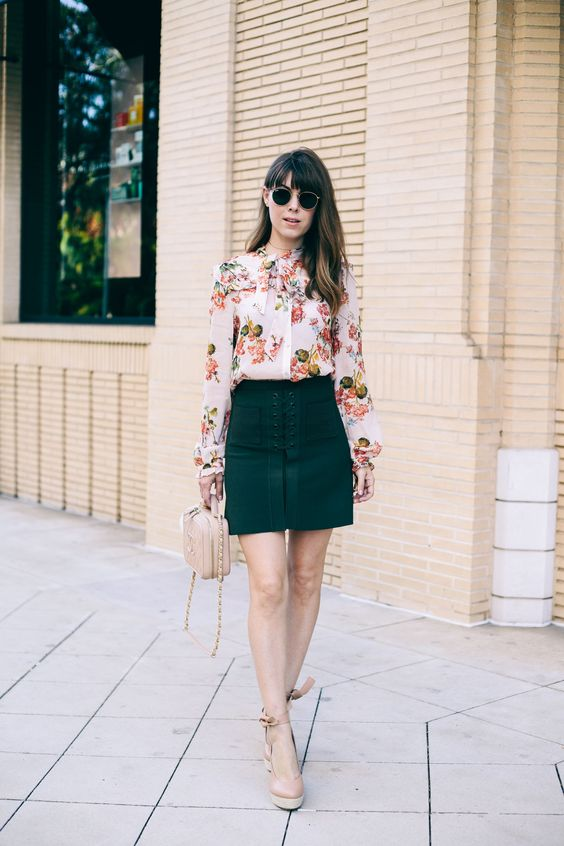a floral blouse with a bow, an emerald lace up skirt and neutral platform heels