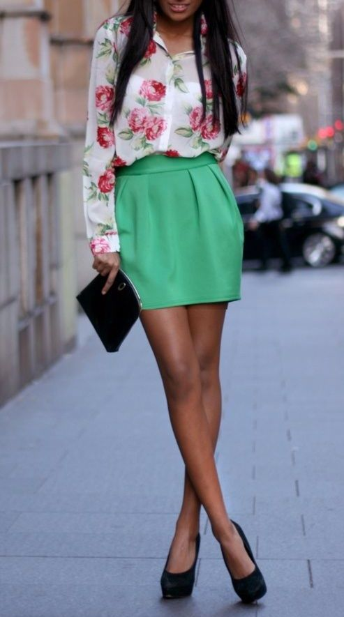 a green mini skirt, a floral blouse and black heels