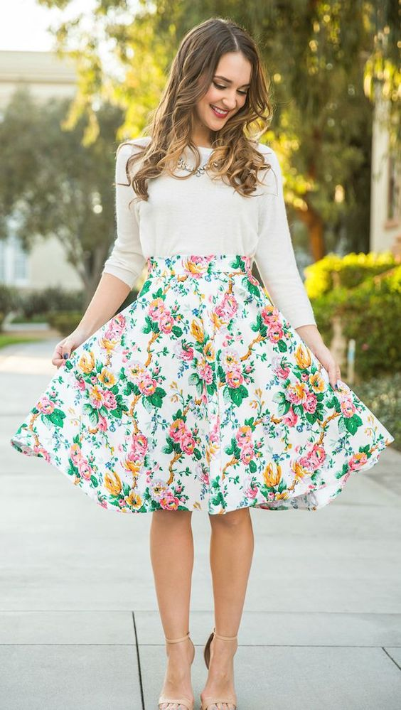 a white long sleeve, a bold floral skirt and nude heels