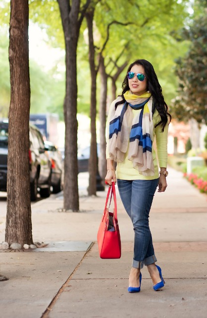 With yellow shirt, colorful scarf, cuffed jeans and red bag