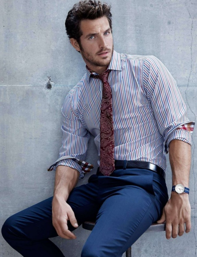 navy pants, a striped blue and red shirt and a burgundy pattern tie
