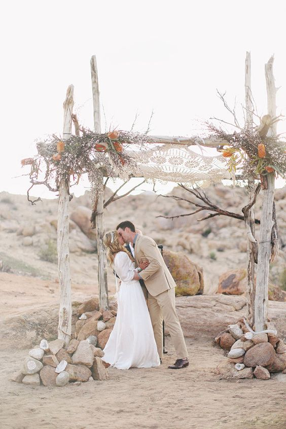 whitewashed wooden chuppah with a macrame hanging above, feathers and flowers