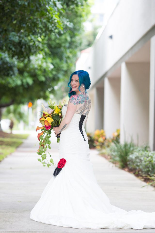 The bride was rocking a strapless fit and flare wedding dress with black lacing and bold blue hair