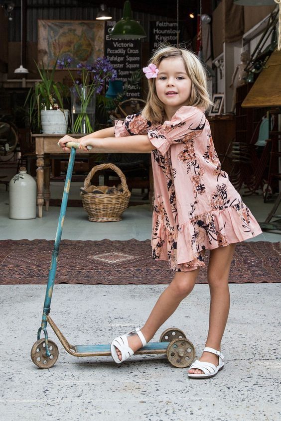 a pink floral dress with half sleeves and white sandals