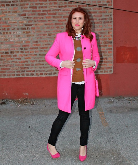 With printed sweatshirt, black pants and hot pink coat