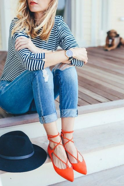 With striped shirt, distressed jeans and hat