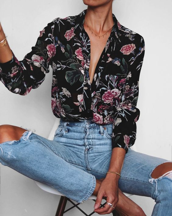 a black floral blouse, ripped blue jeans