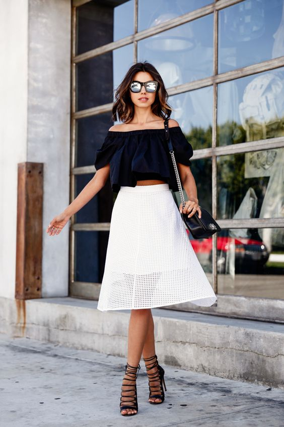 a black off the shoulder, a white perforated midi skirt, black lace up heels