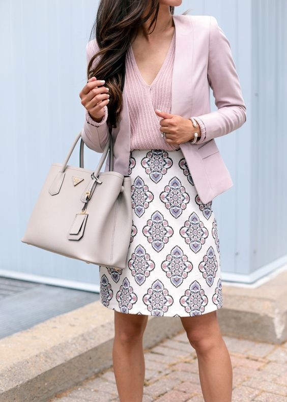 a pink V-neck top, a pink blazer and a patterned skirt