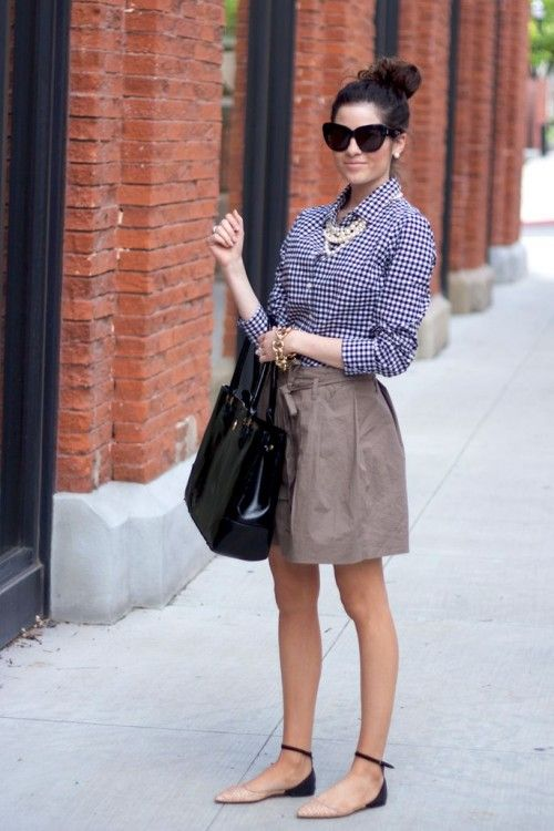 a tan skirt, a blue gingham shirt, nude and black flats