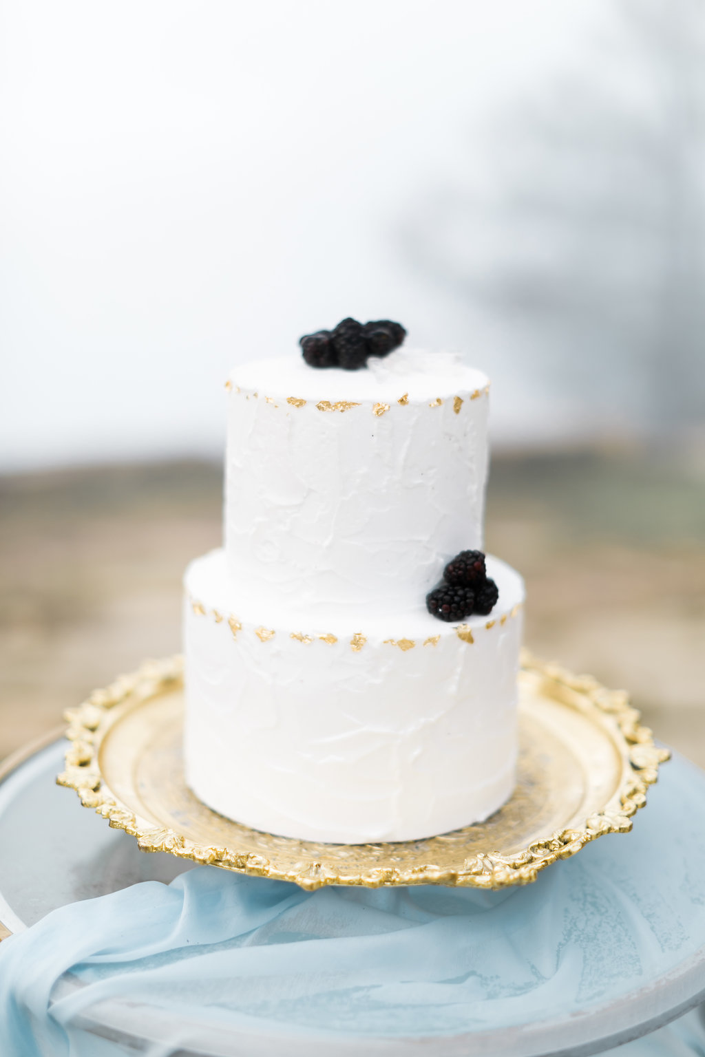 simple wedding cakes with gold - photo by Natalie Schutt http://ruffledblog.com/misty-dream-vow-renewal-at-knapps-castle