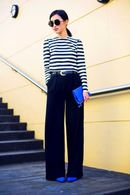 With striped shirt, black wide-leg trousers and clutch