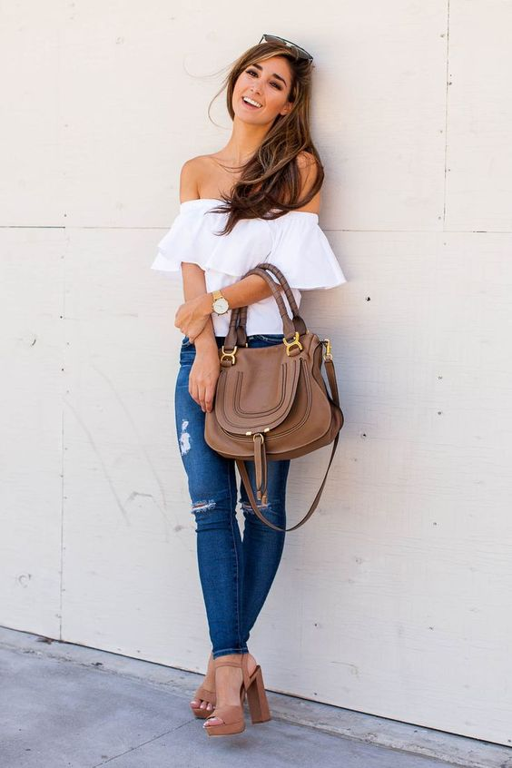 a white off the shoulder ruffled top, ripped jeans, brown heel sandals and a bag