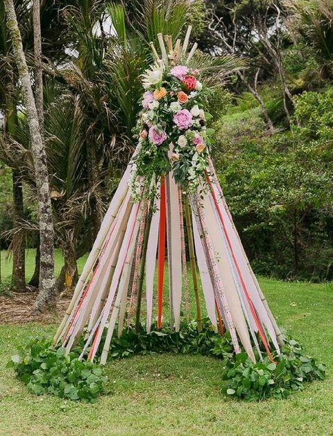 bold ribbon teepee with lush flowers on the top