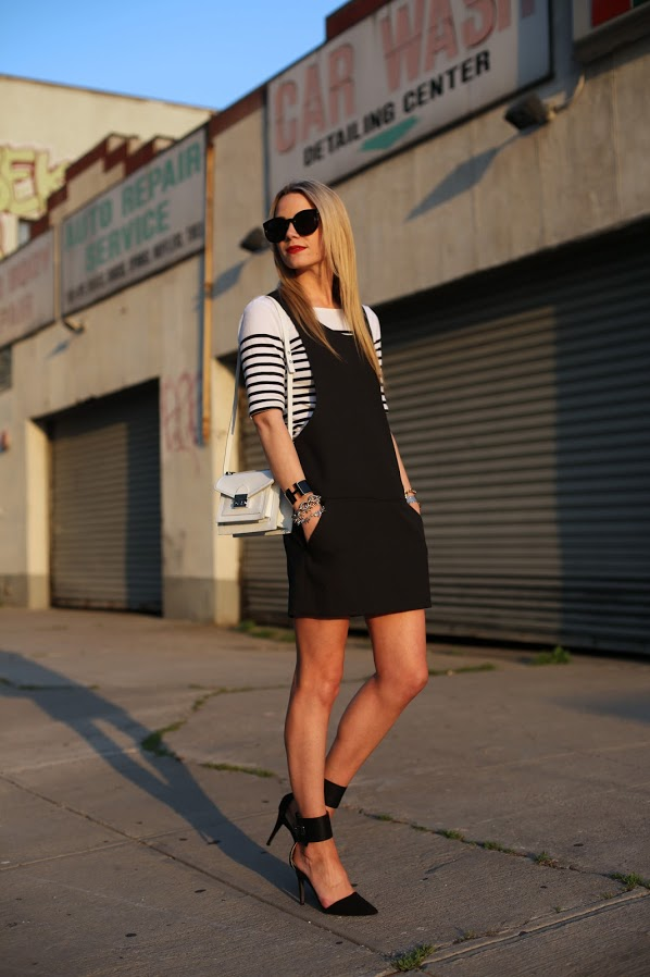 a black overall,a striped top and pointed black shoes