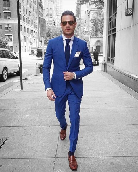 With white shirt, navy blue tie, cobalt blue jacket and brown shoes