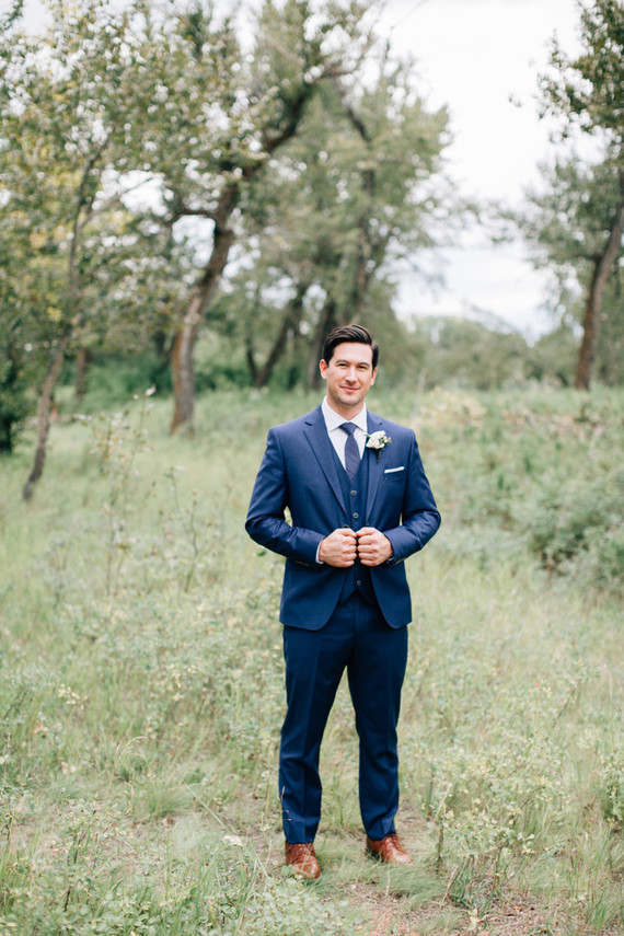 The groom was wearing a stylish navy suit with a vest and tie and ocher shoes for a stylish look