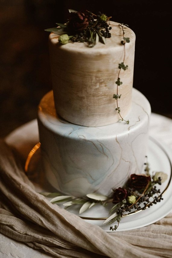 The hand painted marble wedding cake was topped with flowers