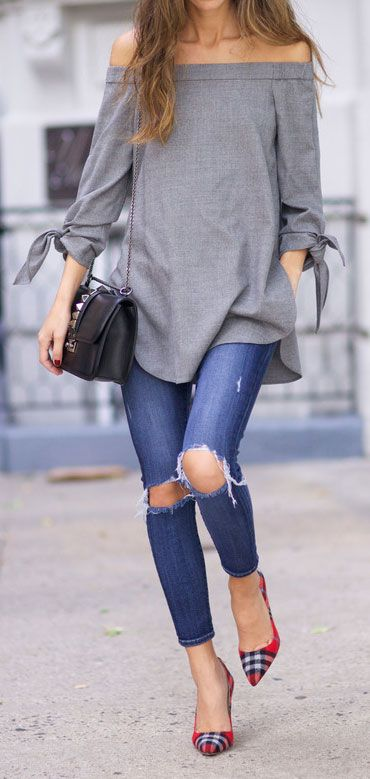 ripped blue jeans, a grey off the shoulder tunic and plaid heels