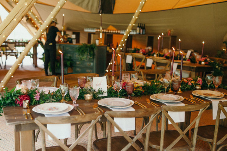 The wedding tables were decorated with greenery and flower garlands and there were colored glasses