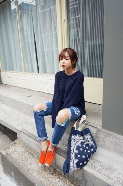 With navy blue sweater, distressed jeans and tote