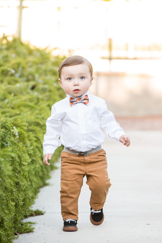 ocher pants, a white shirt, a checked bow tie and black sneakers