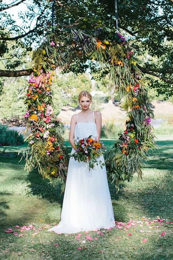 a bright floral wreath backdrop for summer wedding ceremony