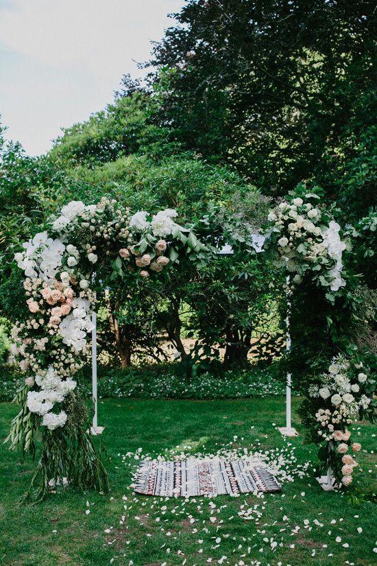 super lush wedding arch with lots of greenery, blush and white blooms