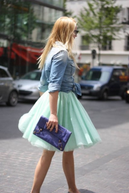 With denim shirt and blue clutch