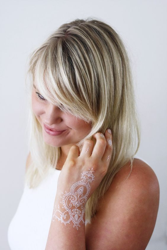 white lacey hand tattoo going on the wrist and fingers