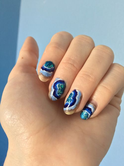 colorful geode-inspired nails in blue, emerald and orange