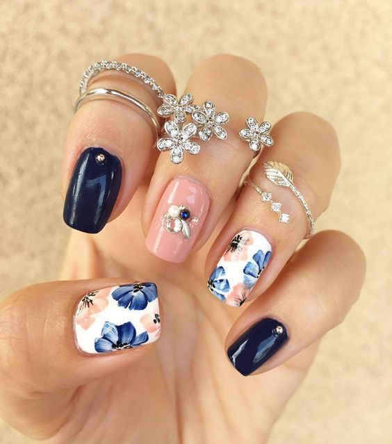 navy and peach glossy nails with rhinestones and two floral nails in blue and peach
