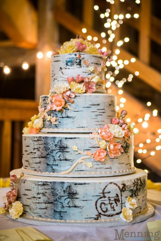 a multi-tiered birch cake topped with edible flowers