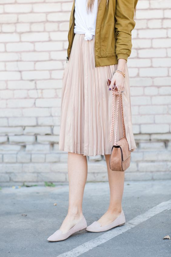 a blush pleated skirt and flats, a white tee and a mustard bomber