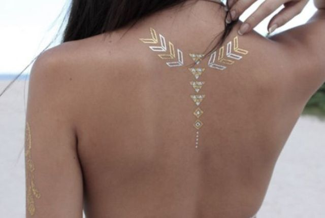 gold and white geometric henna tattoo on the upper part of the back
