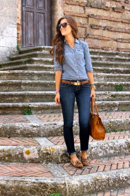 With blue shirt, cuffed jeans and brown bag