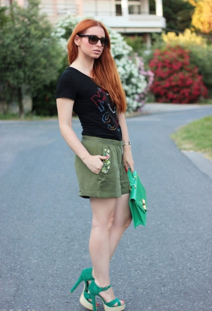 With black t-shirt, olive green shorts and green bag
