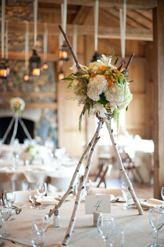 birch poles with a floral arrangement on top