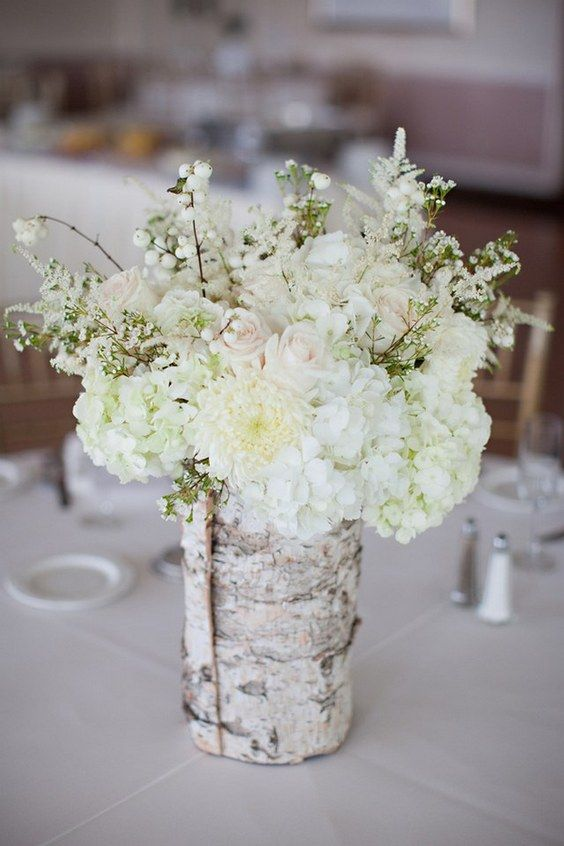 white hydrangeas and blush roses and a vase wrapped with birch bark