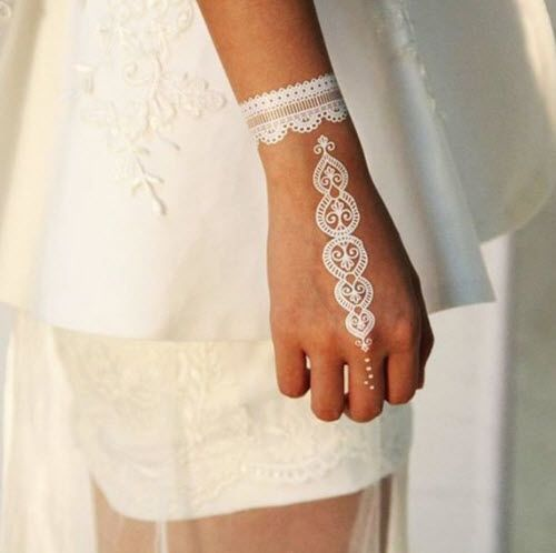 a lacey henna tattoo on the hand and wrist for a bride