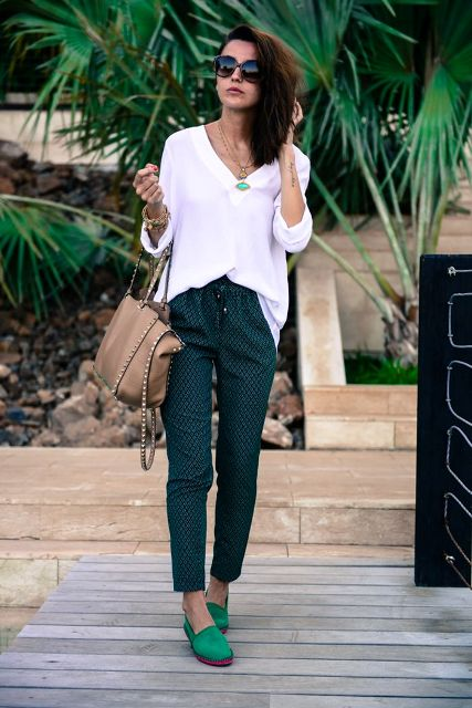 With white oversized shirt, printed pants and beige bag