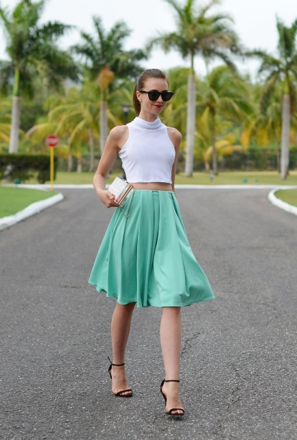 With white crop top, black sandals and clutch