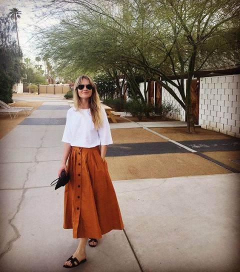 With white loose shirt, black sandals and clutch