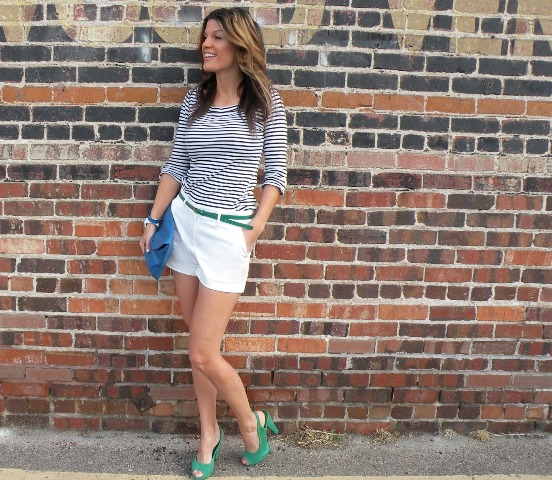 With striped shirt, white shorts, green belt and blue clutch