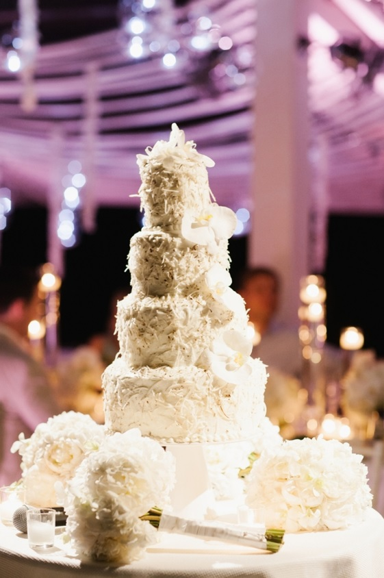 The wedding cake was textural and white with coconut and displayed with white florals