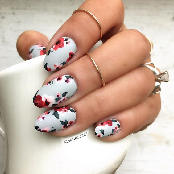white matte manicure with bold red blooms