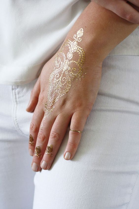 delicate gold henna tattoo on the hand and fingers