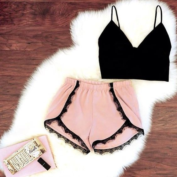 pink shorts with a black lace trim and a crop black top