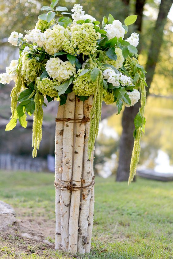 birch branches secured with twine and hydrangeas on top for the aisle decor